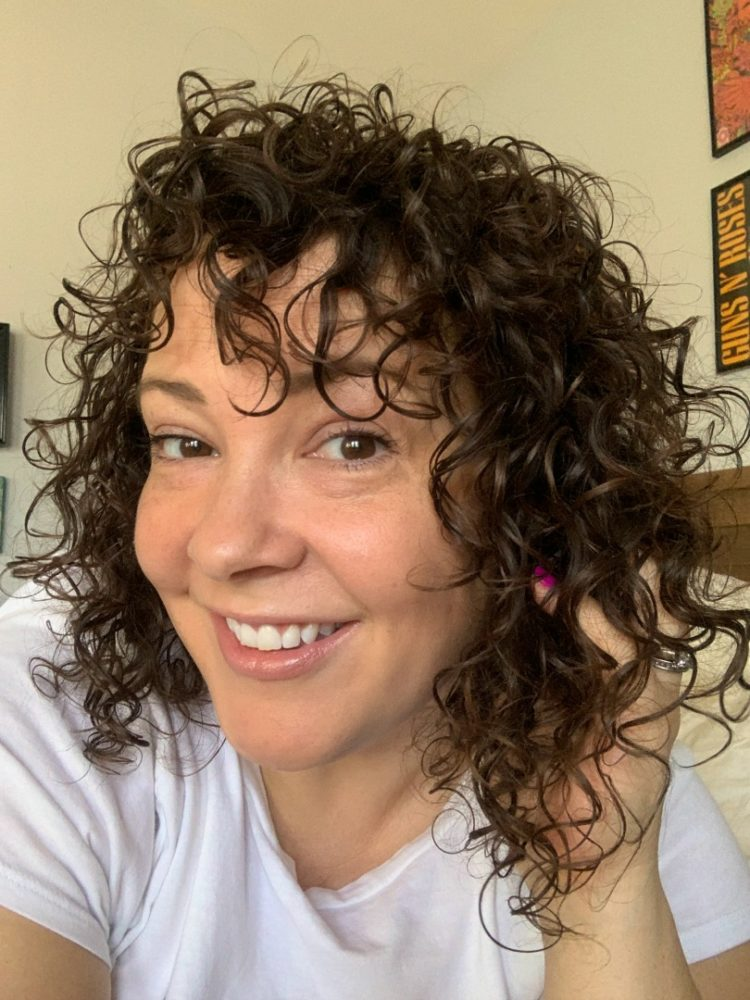 woman smiling at camera with her hand in her dark curly hair