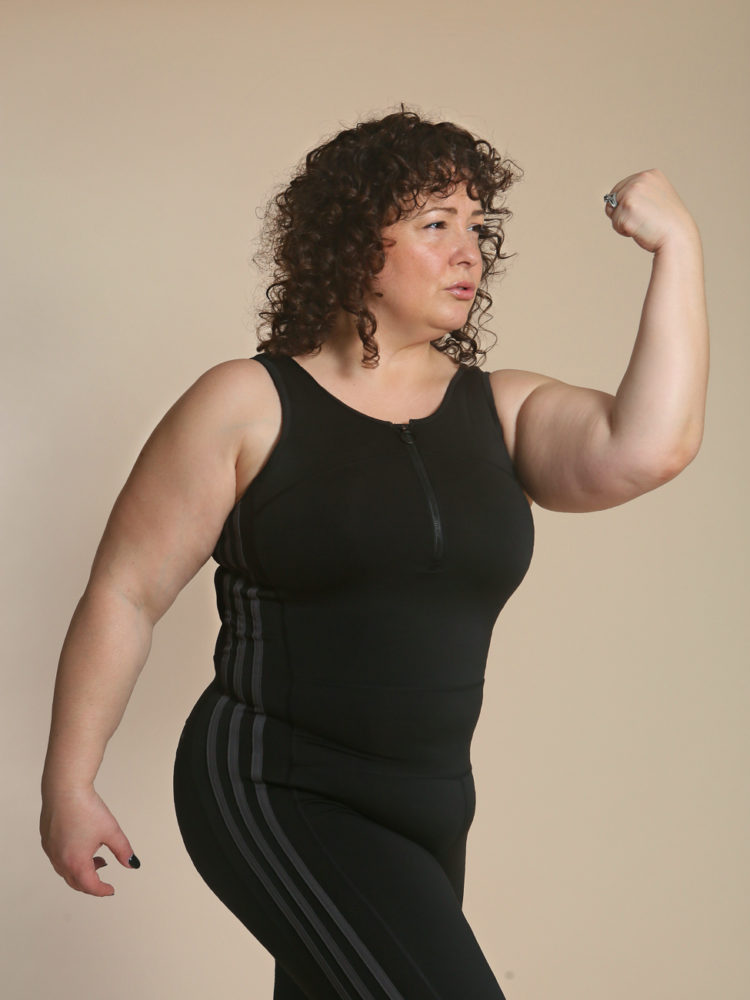 Woman flexing in a black unitard