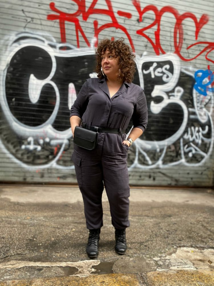 Alison of Wardrobe Oxygen in a gray boilersuit with a black leather belt bag and silver hoops from Jenny Bird
