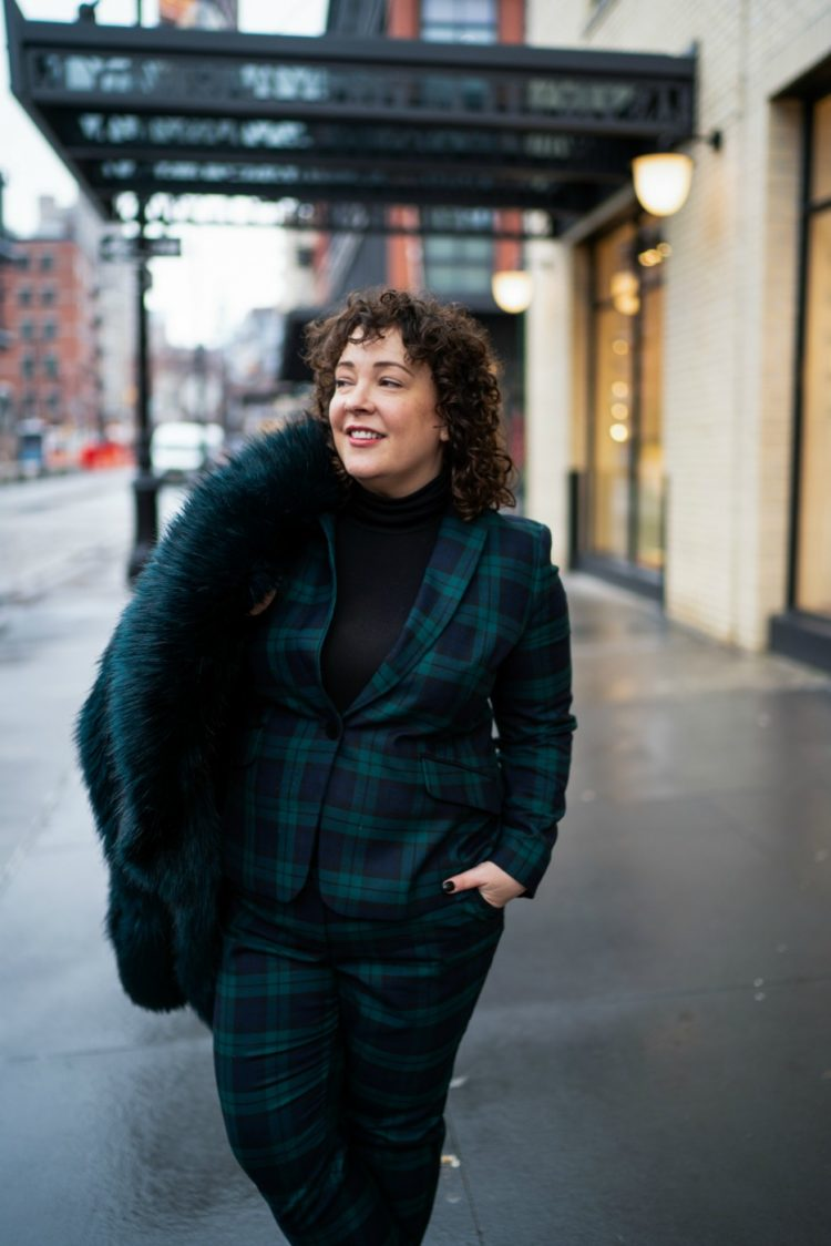 Styling a black watch plaid pantsuit for women with a black turtleneck and dark green faux fur jacket