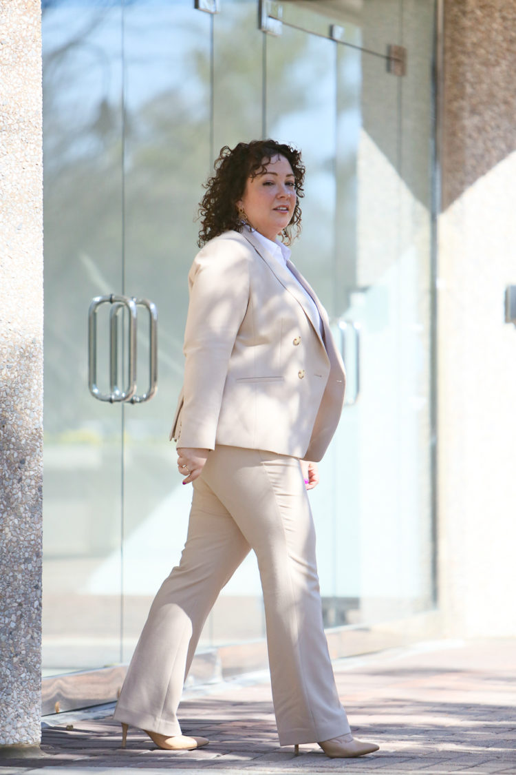 Woman walking out of an office building in a tan colored pantsuit