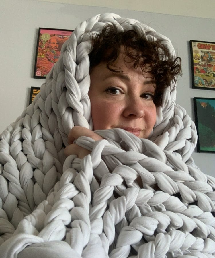 alison wrapped up in a pale gray wide knit blanket called the tree napper