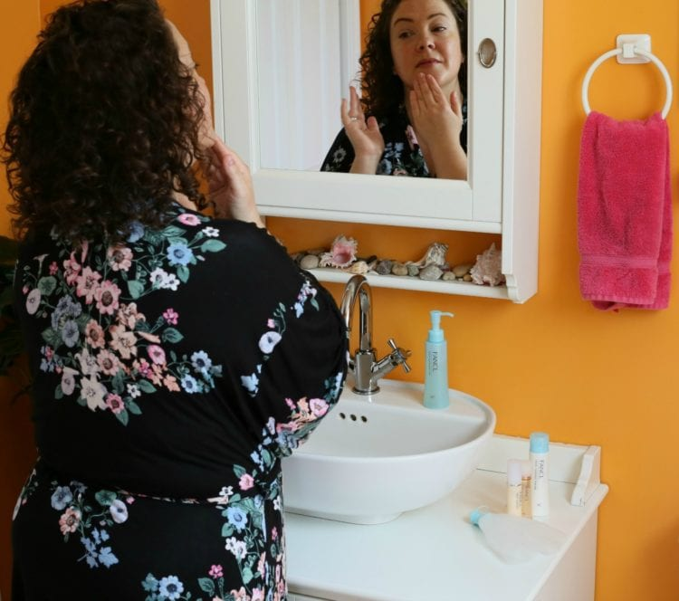 woman in a floral bathrobe looking at her reflection in a mirror as she applies moisturizer to her face