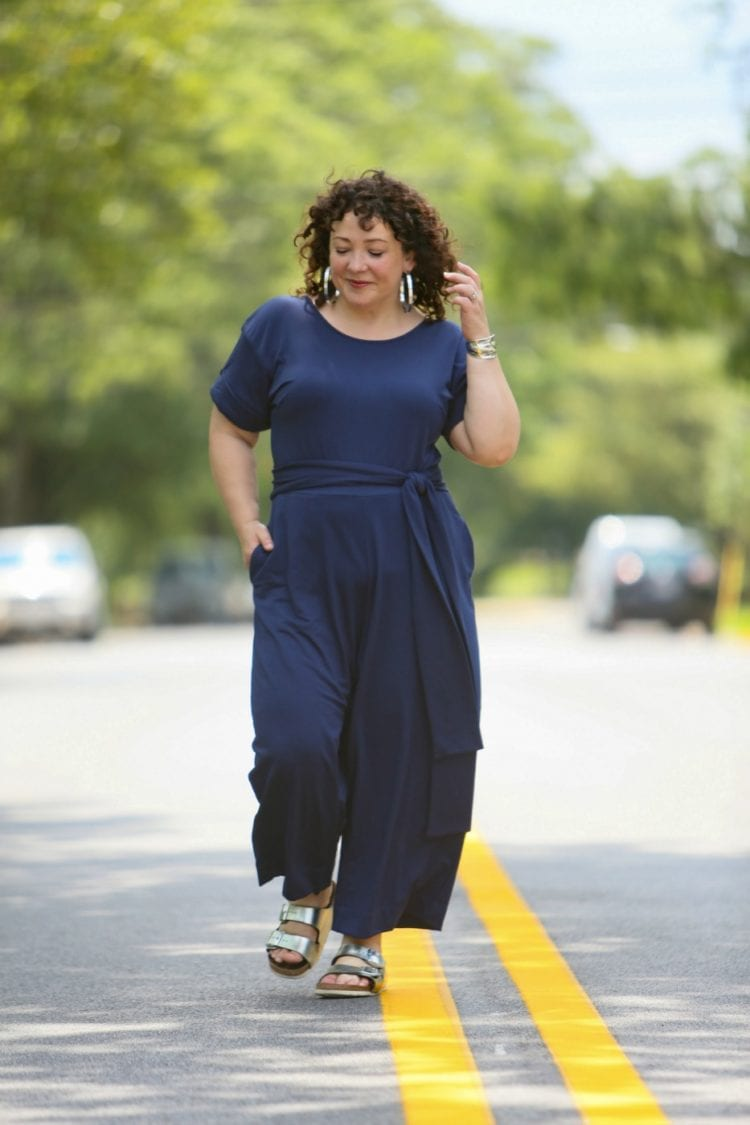 Woman in a dark blue belted jumpsuit from Ori styled with silver metallic Birkenstocks