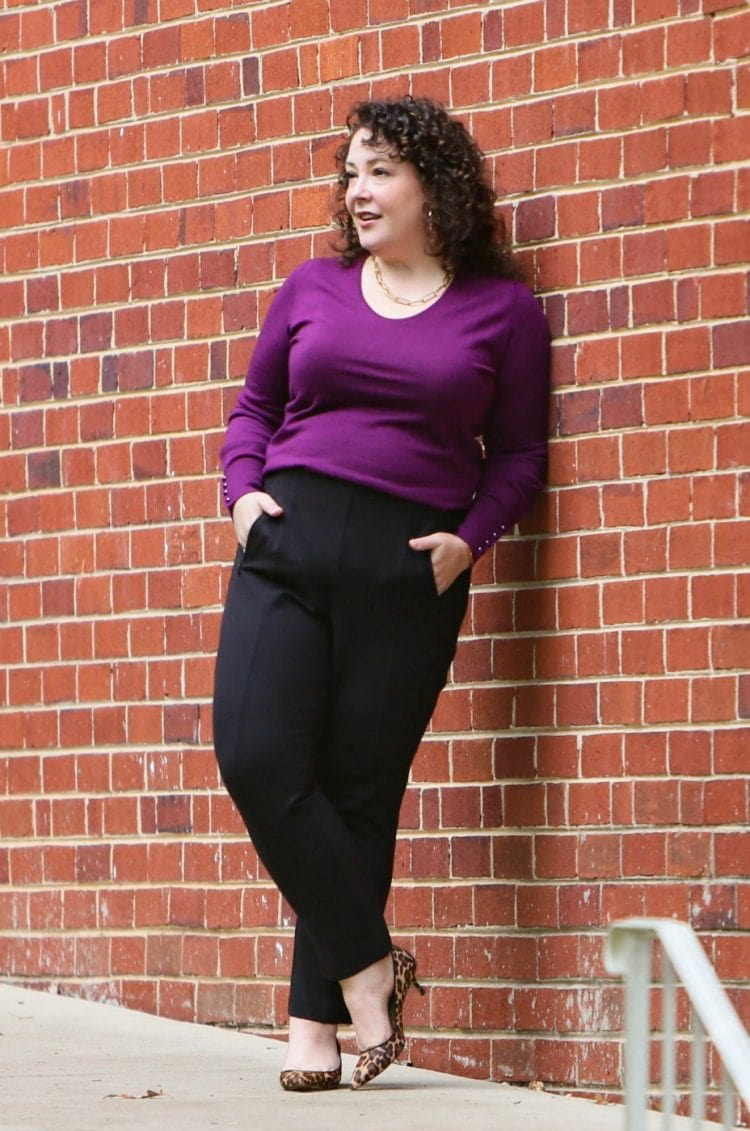 Woman in black ponte work pants and a purple merino v-neck sweater leaning against a brick wall