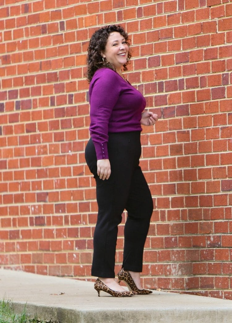 woman in black ponte ankle pants and a purple sweater smiling in front of a brick wall