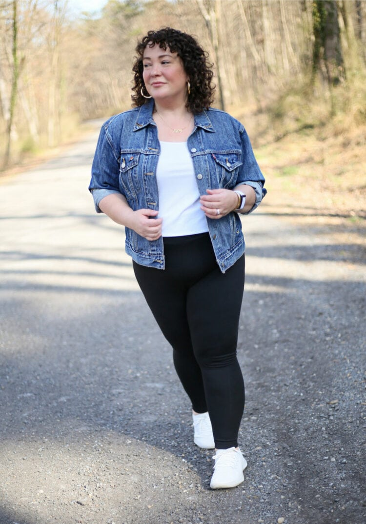 Alison of Wardrobe Oxygen laughing and dancing on a gravel road while wearing black leggings with a denim jacket and white Allbirds sneakers