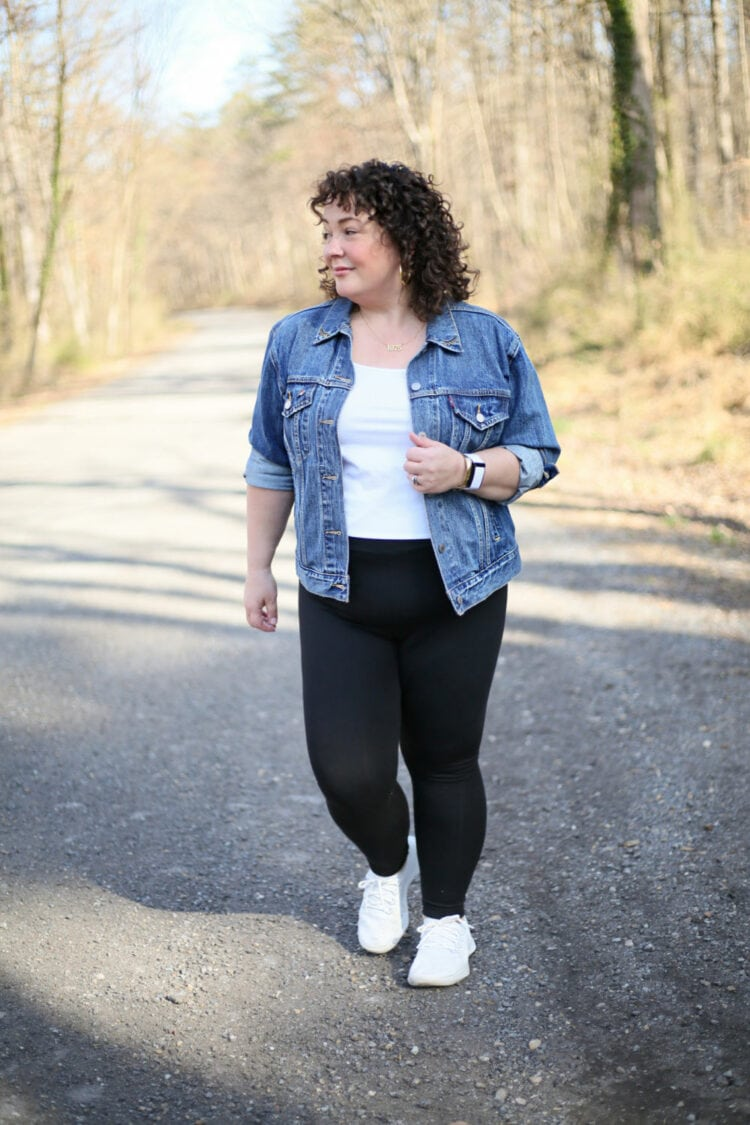 Alison of Wardrobe Oxygen walking down a gravel road in black plus sized leggings from Pari Passu with a vintage Levi's denim jacket and white sneakers