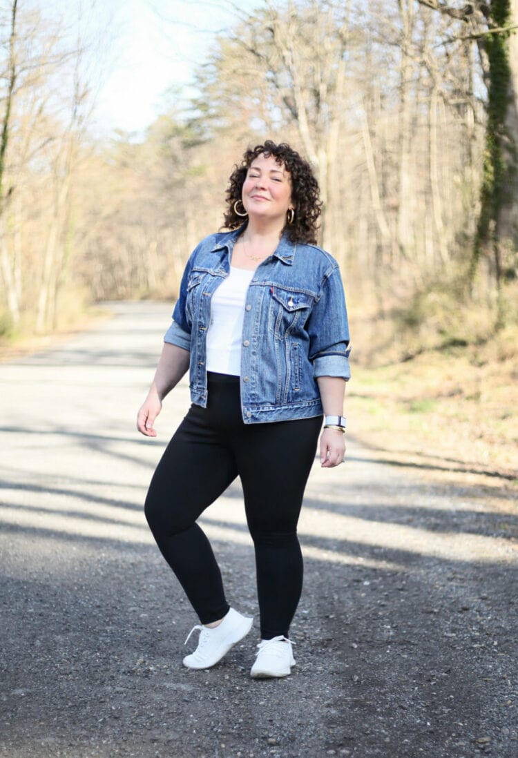 Alison of Wardrobe Oxygen in black leggings, a white tank, and denim jacket grinning while standing on a gravel road through a wood