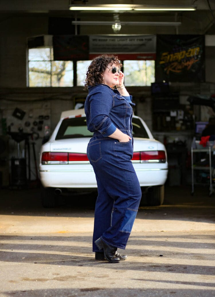 Alison in a dark denim pair of coveralls or a boilersuit standing in front of an auto body shop