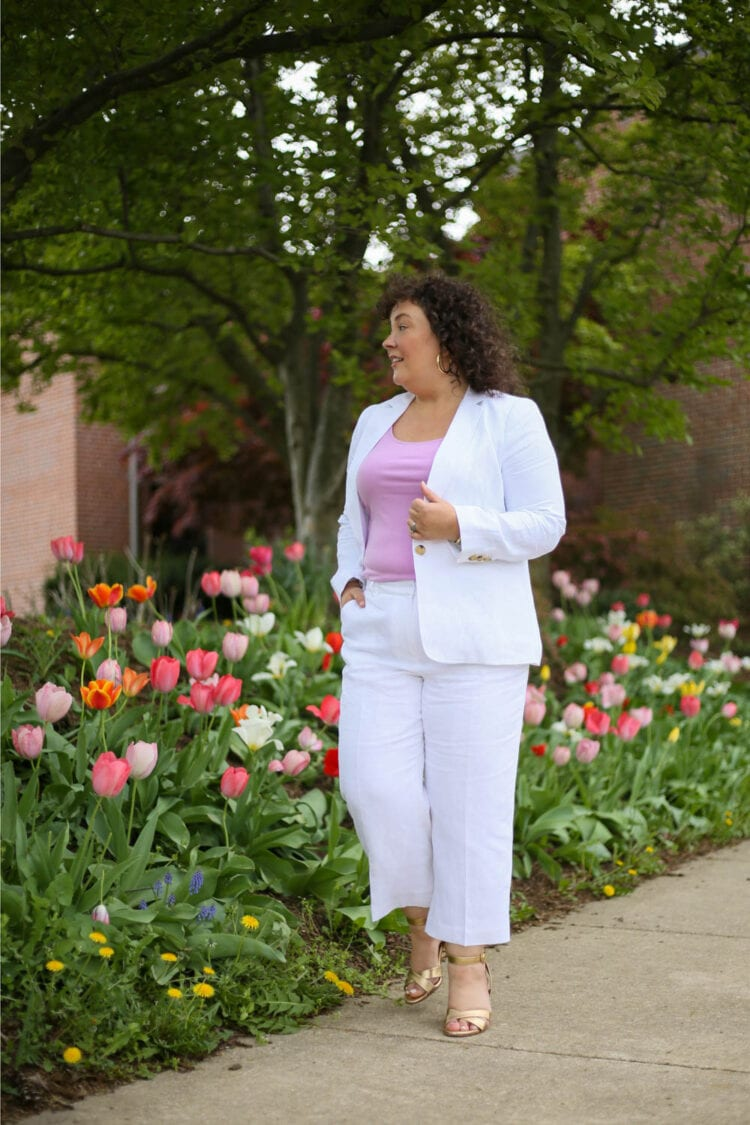 Alison in a Talbots linen blazer and cropped pants with a lavender knit shell underneath, walking along a sidewalk flanked by tulips
