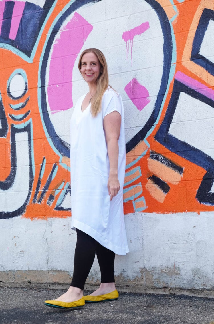 Lissa in the white Tiny Closet Tourist Dress against a colorful brick mural