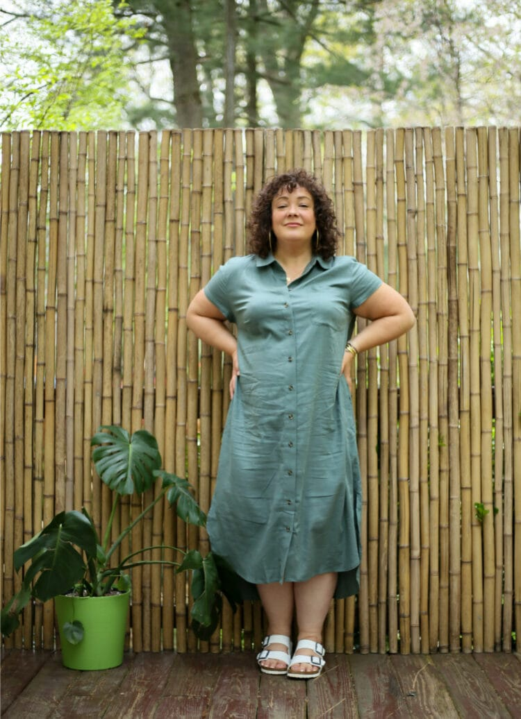 Alison wearing a green linen cap sleeve shirt dress that is midi length. She's wearing it with white Birkenstock Arizona sandals and has her hands on her hips smiling at the camera.