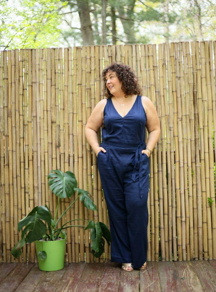 Alison wearing a navy sleeveless linen jumpsuit from Universal Standard that has a v-neck and a self belt. SHe paired it with gold Margaux heeled sandals