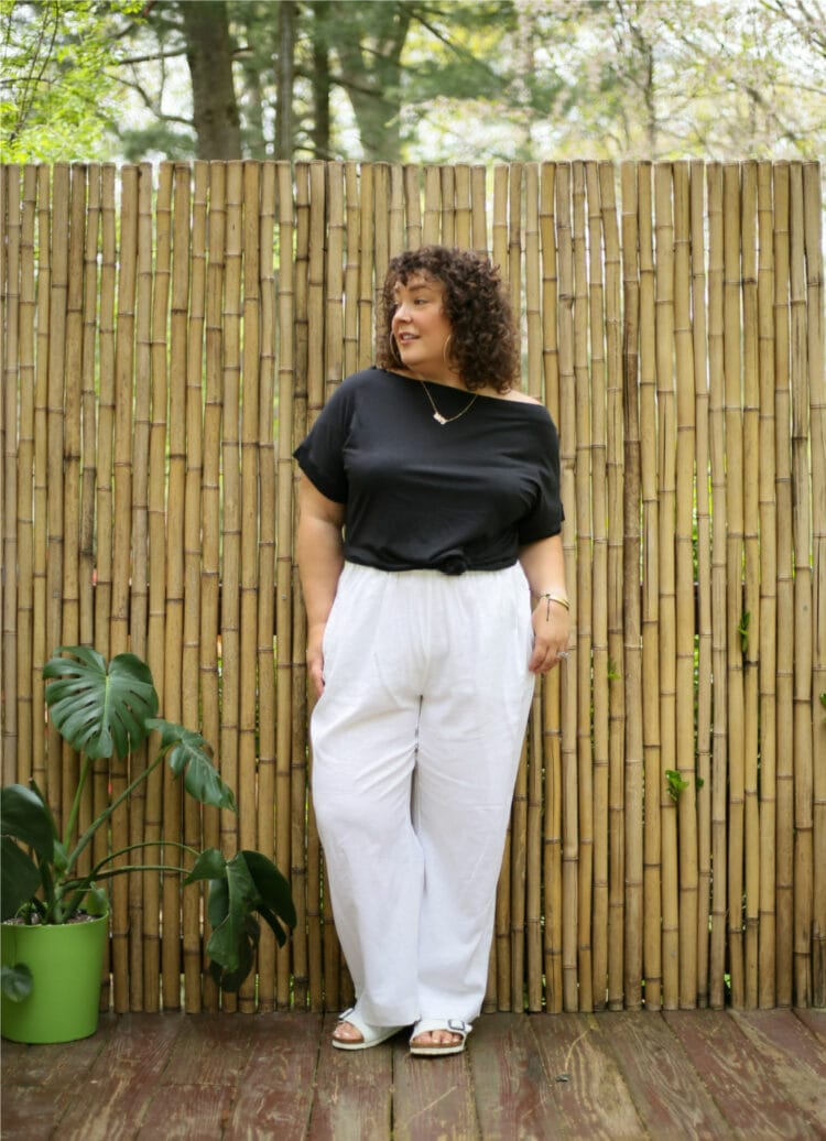 Alison in a black off the shoulder t-shirt knitted at the waist and white linen wide leg pants. She is standing in front of a bamboo wall and looking to the left.