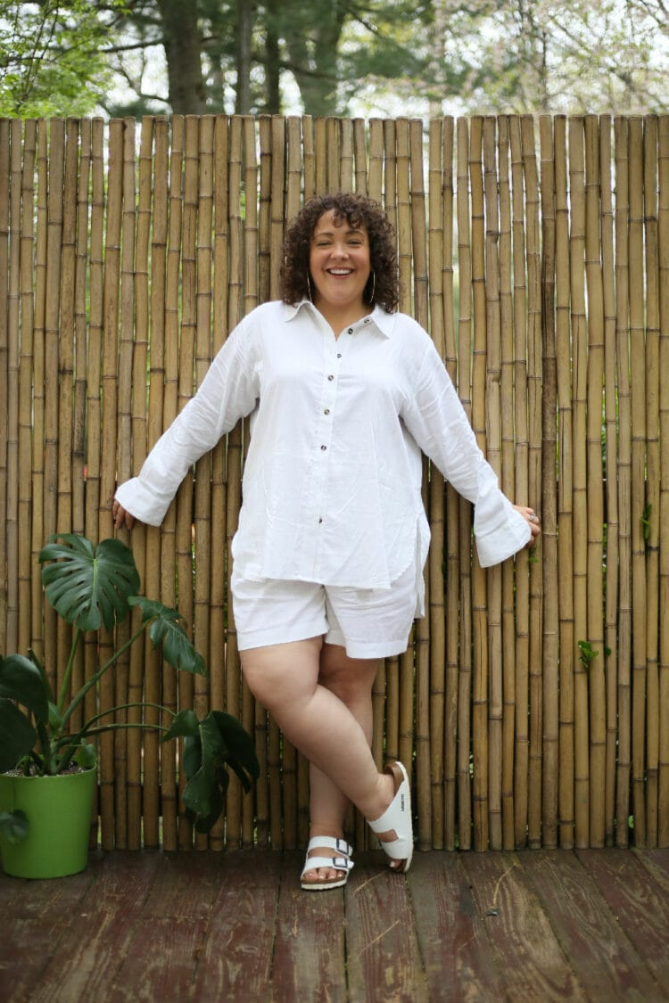 Universal Standard linen long-sleeved shirt and loose above-knee shorts on Alison. She is standing in front of a wall of bamboo with her legs crossed and smiling at the camera.