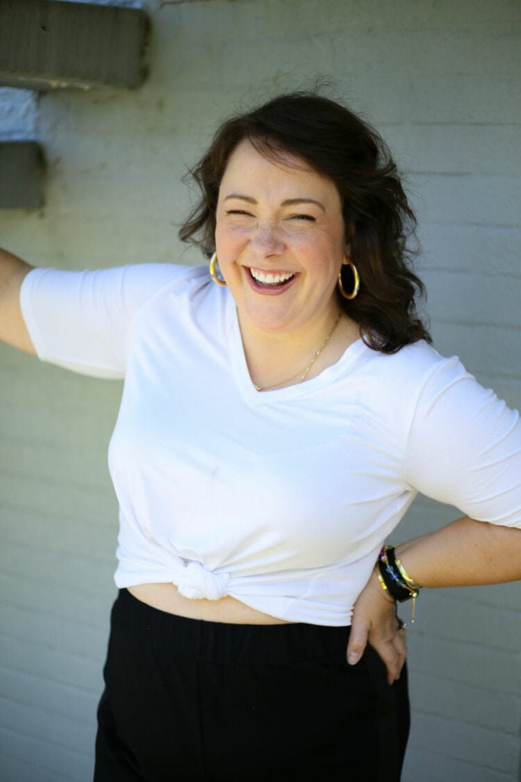 Alison in the Universal Standard Lily Liquid Jersey V-Neck from Universal Standard, tied at the waist. She has one hand on her hip and is laughing to the camera.