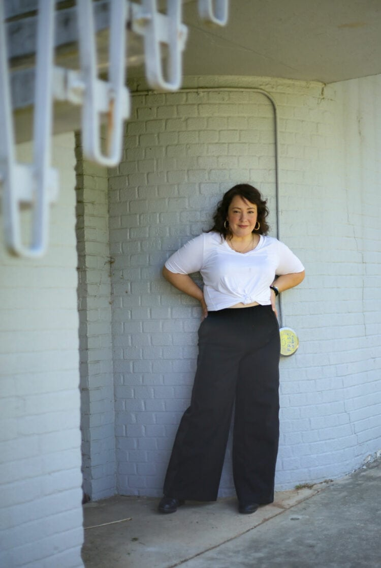 Alison in a white v-neck top tied at the waist with black wide-leg pants from Universal Standard. She is standing against a gray brick wall with her hands on her hips.