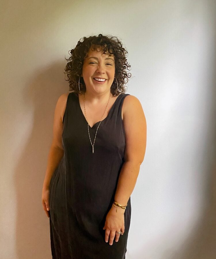 Alison wearing a black sleeveless v-neck cupro dress. She is smiling at the camera leaning against a wall