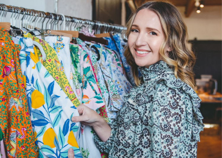 Image of Amy Voloshin in a blue and white printed top standing next to a rolling rack full of Printfresh sleepwear