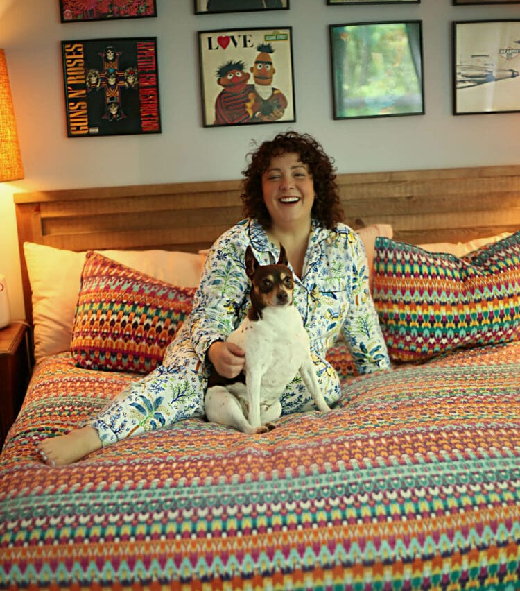 Alison wearing white and blue printed cotton full length long sleeved pajamas from Printfresh. She is sitting on her bed which is covered by a rainbow striped quilt and is cudding her small fox terrier mix dog Oscar.