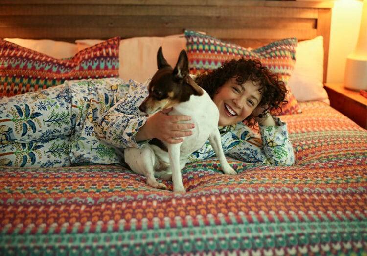 Alison lying on her bed snuggling with her dog