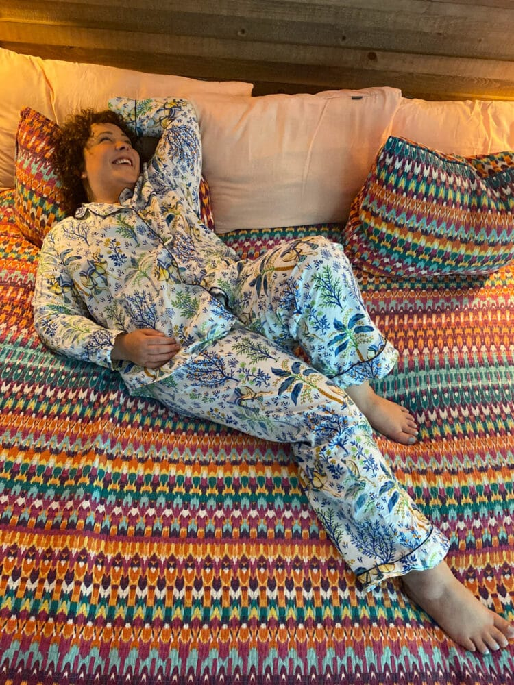 Alison lying on her bed laughing while wearing organic poplin pajamas from Printfresh