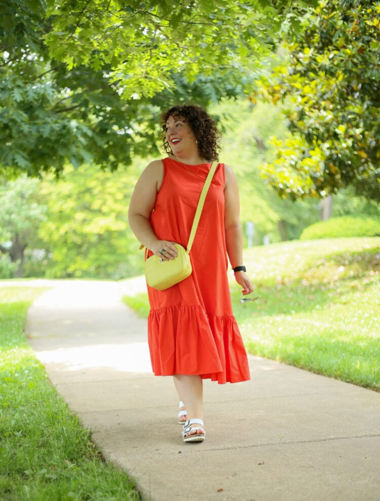 Alison wearing the Christopher John Rogers for Target Orange Shift Dress with a lemon yellow crossbody bag. She is walking down a sidewalk and smiling off camera