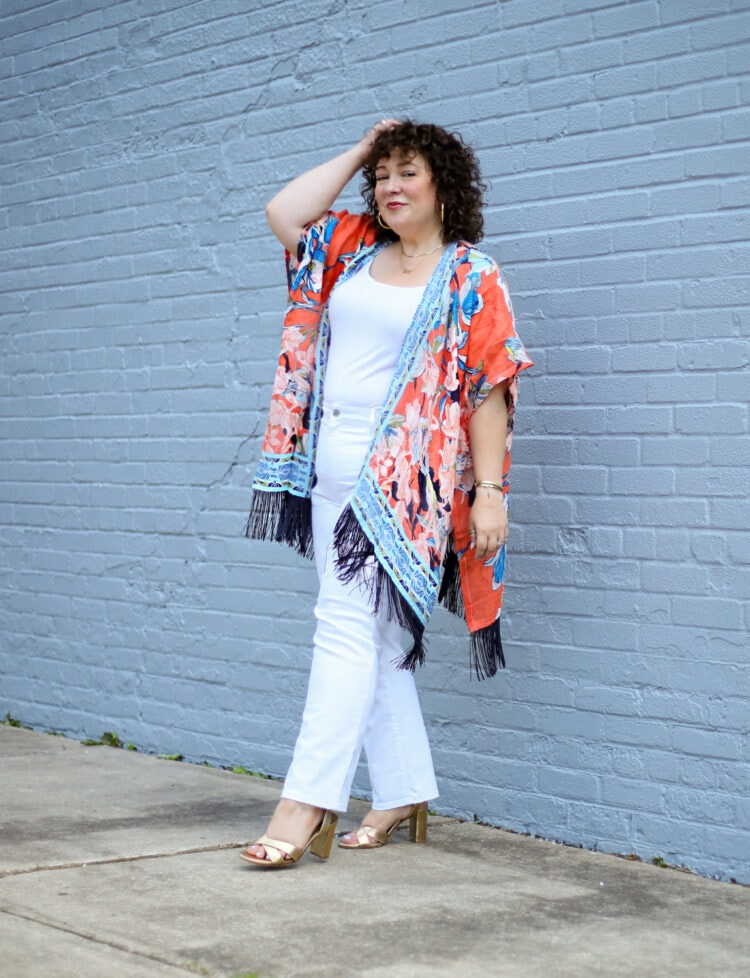 Alison of Wardrobe Oxygen wearing a linen ruana from Chico's in an orange and blue print with black tassels. She is walking away from a gray wall, her hand in her hair