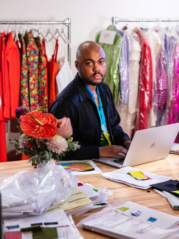 Fashion designer Christopher John Rogers sitting in his studio with racks of his colorful clothing behind him. He is wearing black jacket over a tropical print shirt. He is typing on an Apple computer and staring at the camera.