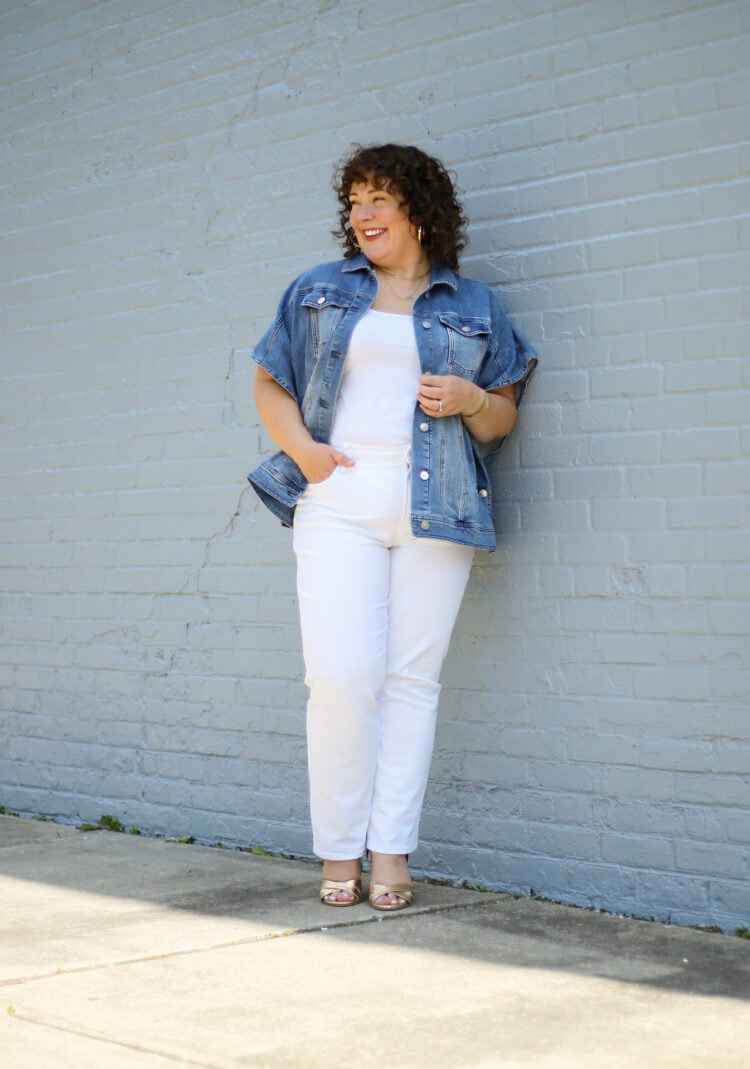 Alison wearing a summer ruana of denim from Chico's with white jeans and a tank. She is laughing and looking at something off camera