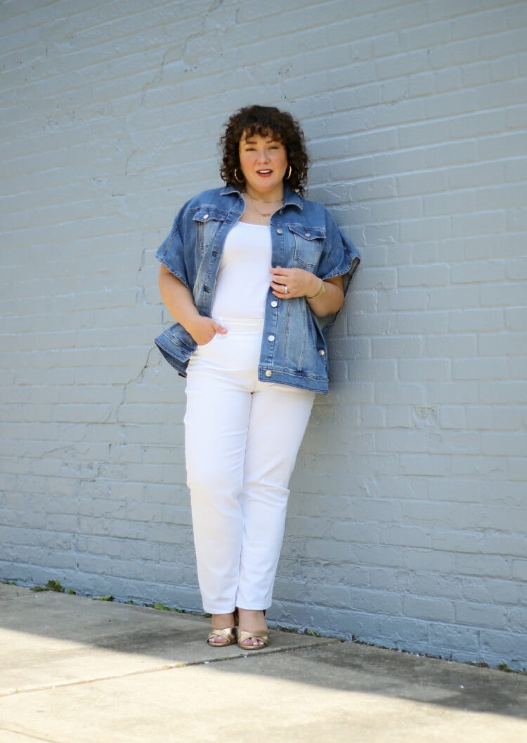 Alison of Wardrobe Oxygen wearing a denim ruana from Chico's with white straight jeans and a white tank and gold Margaux Uptown Sandals. She is standing against a pale gray brick wall, one hand in a pocket, looking at the camera.