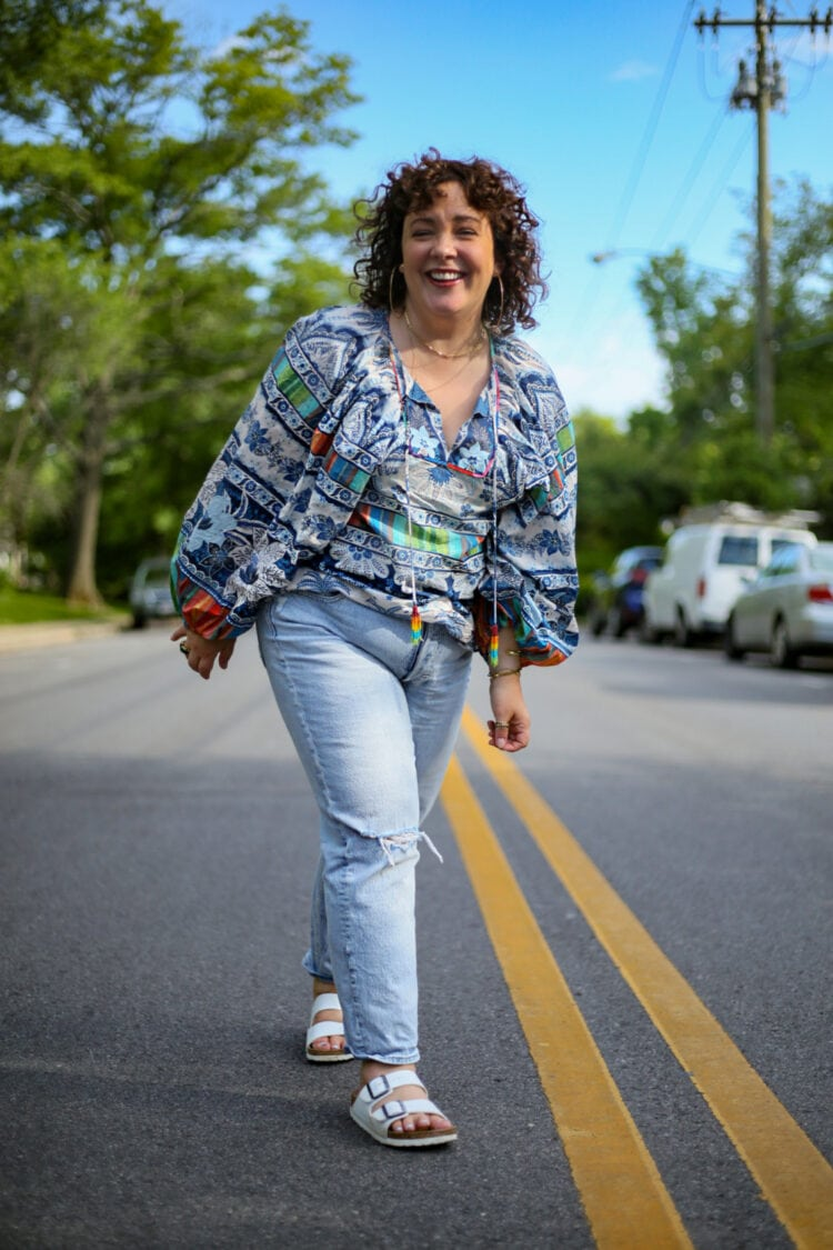 Alison walking towards the camera laughing while wearing a blue and white print Farm Rio top and faded distressed Gap jeans