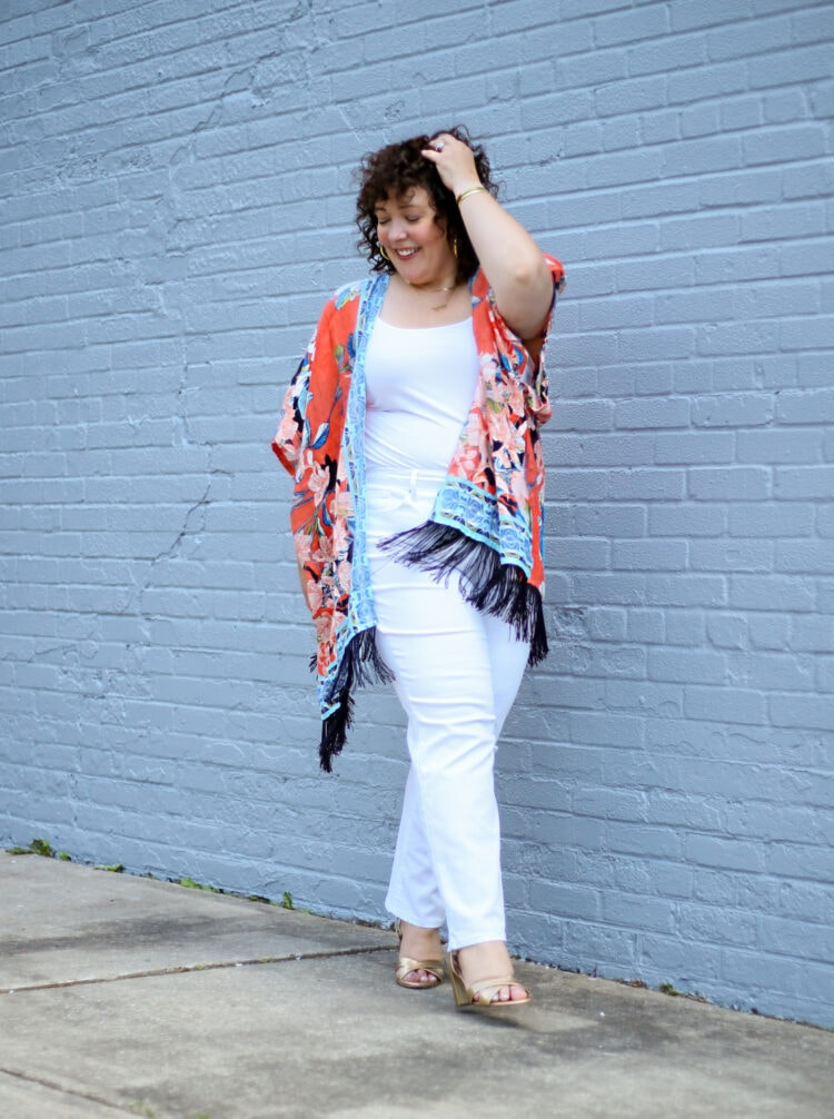 Alison in an orange and blue linen ruana with white jeans and a white tank and gold Margaux Uptown sandals