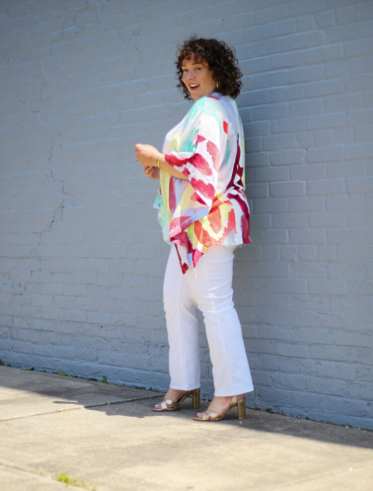 Alison of Wardrobe Oxygen in a lightweight summer ruana from Chico's that is white with a watercolor brush stroke design in reds and greens and yellows. She is wearing it with white jeans and is walking away from the camera but looking back and smiling