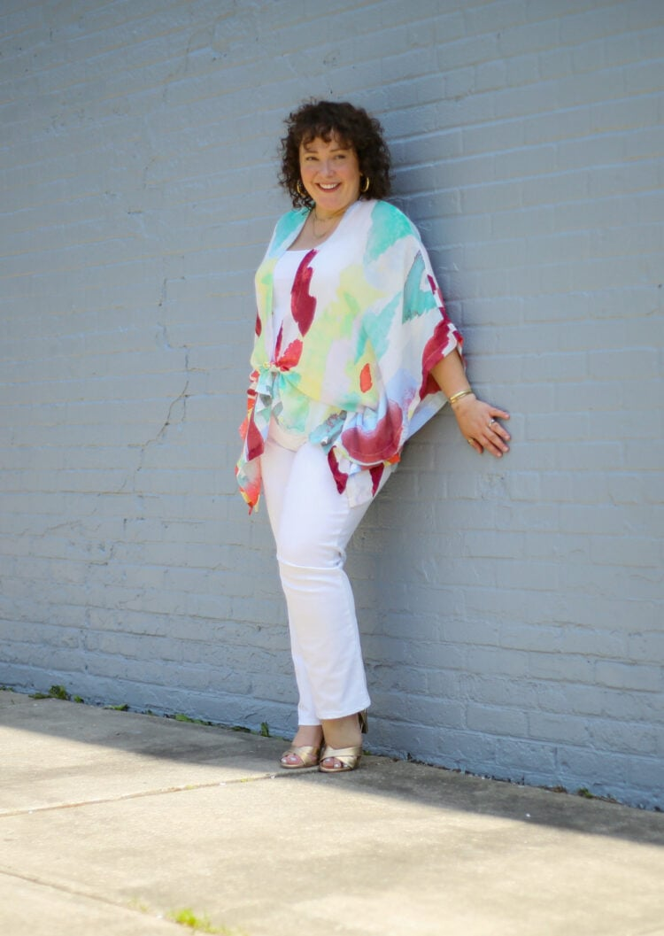 Alison of Wardrobe Oxygen styling a summer ruana from Chico's with white jeans. She is leaning against a gray wall and looking to the left