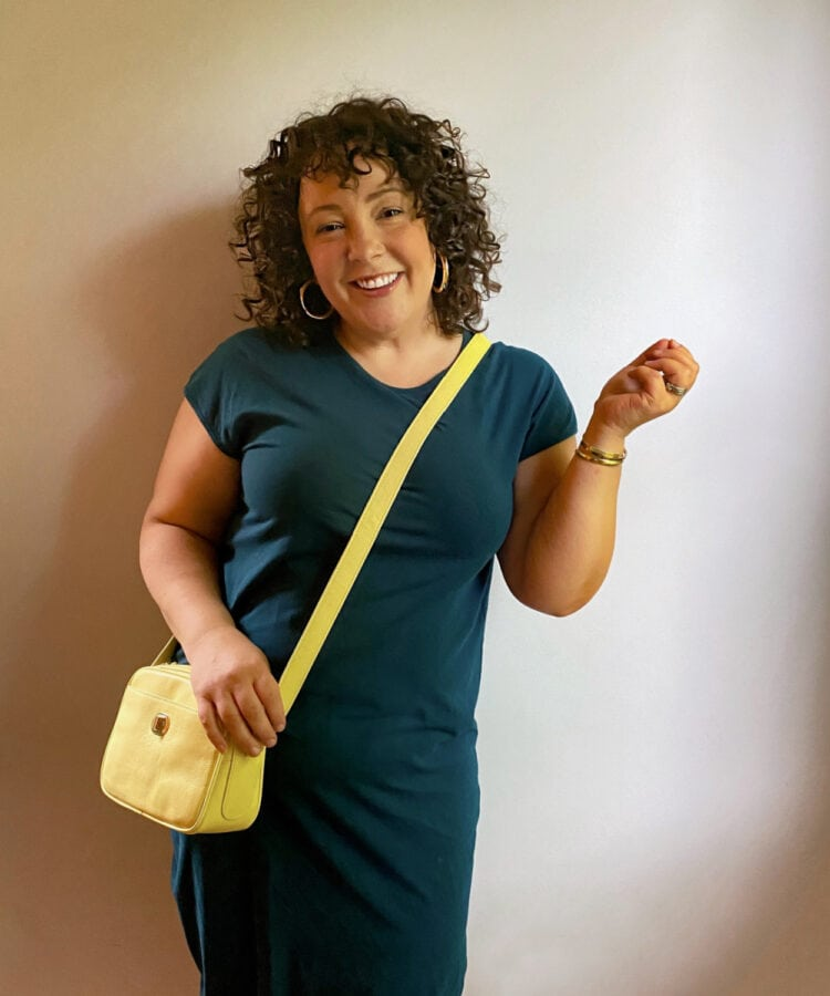 Alison in a teal knit t-shirt dress with a yellow crossbody bag