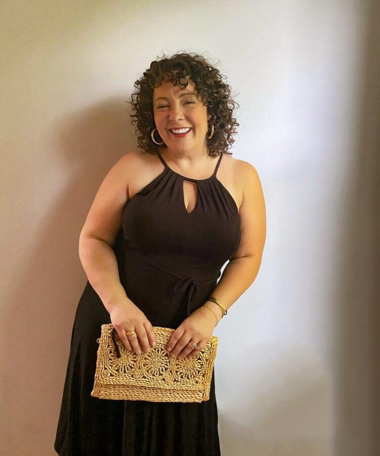 Alison in a black halter neck knit dress holding a raffia clutch purse