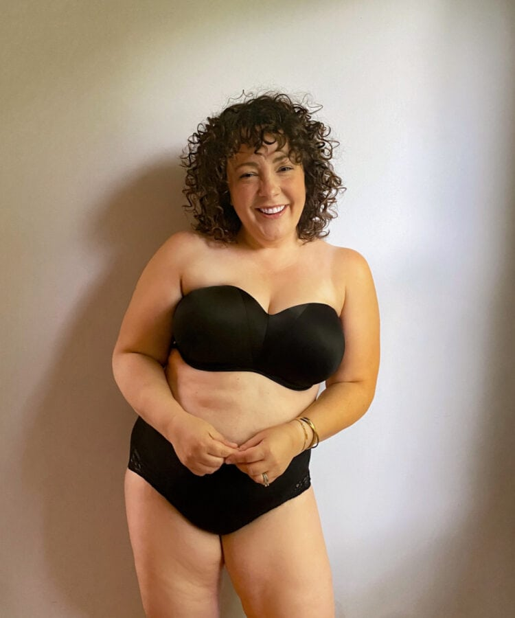 Alison wearing a black Soma Stunning Starlet strapless bra with black briefs. She is standing against a wall and smiling at the camera