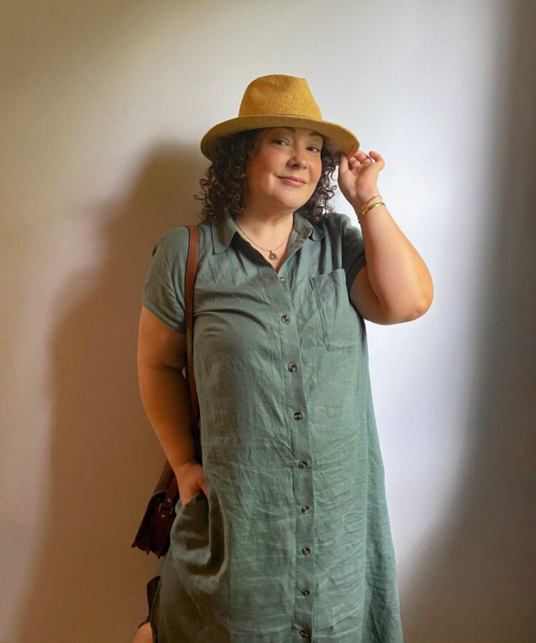 Alison wearing a sage green linen shirtdress with cap sleeves. She is wearing a straw hat and touching the brim, a brown handbag on her shoulder
