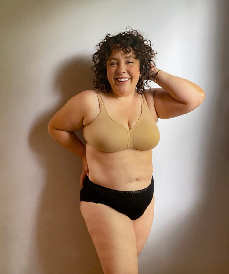 Alison in the Soma Full Coverage Wireless Unlined Bra in Warm Amber and a pair of black underwear briefs. She is standing in front of a wall smiling at the camera, her hand touching her hair