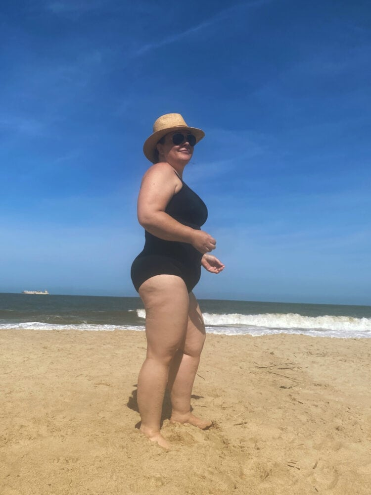 Is this the best swimsuit for women over 40? Alison of Wardrobe Oxygen models the Lands' End Tugless tank in black. She is standing on the beach facing to the right and is smiling at the camera.