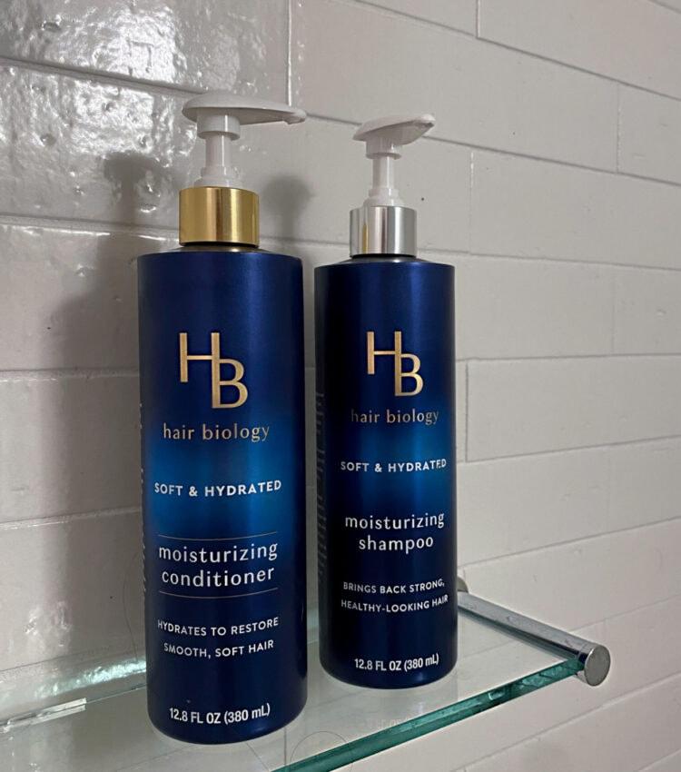 Bottles of Hair Biology Moisturizing shampoo and conditioner on a glass shelf inside a white tiled shower.