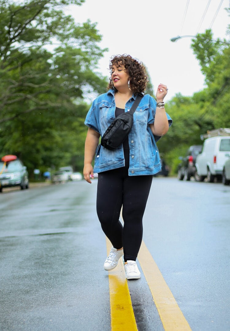 Alison standing in the middle of a street. She is wearing a hip length sleeveless denim jacket and black leggings. She has on white Adidas Superstar sneakers and has a black belt bag across her body.