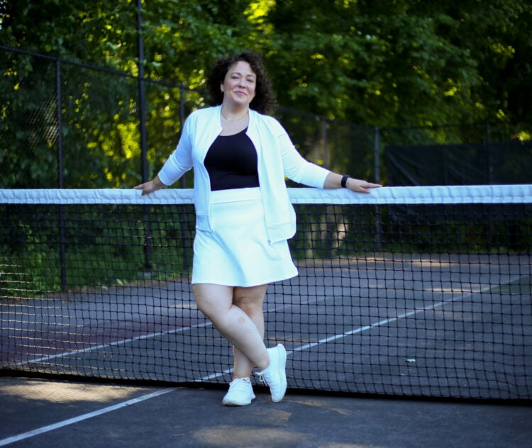 Alison of Wardrobe Oxygen in a white bomber jacket and skort with a black tank and white Allbirds sneakers