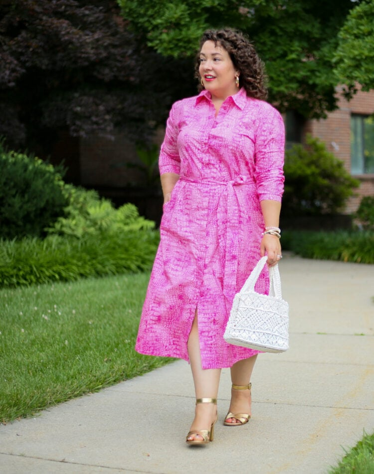 Alison in a pink snakeskin cotton poplin shirtdress from Chico's Black Label collection. She is walking down a sidewalk looking away from the camera.