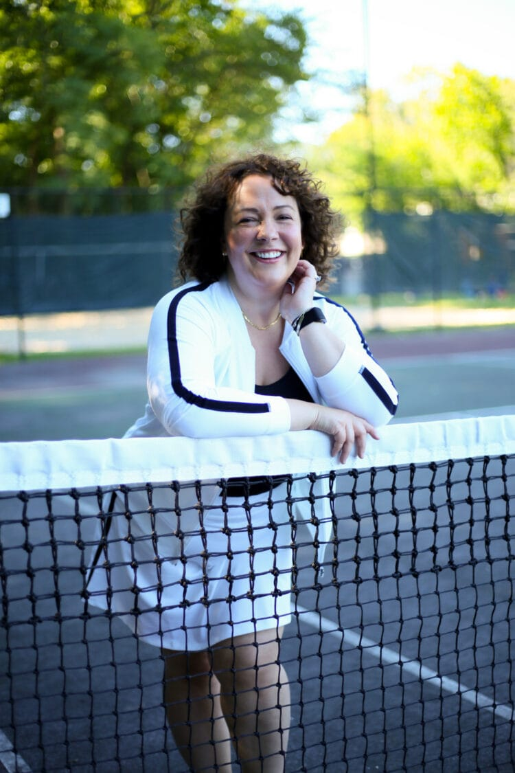 Alison in a white knit bomber jacket and matching skort from Talbots. She is leaning against a tennis net smiling at the camera