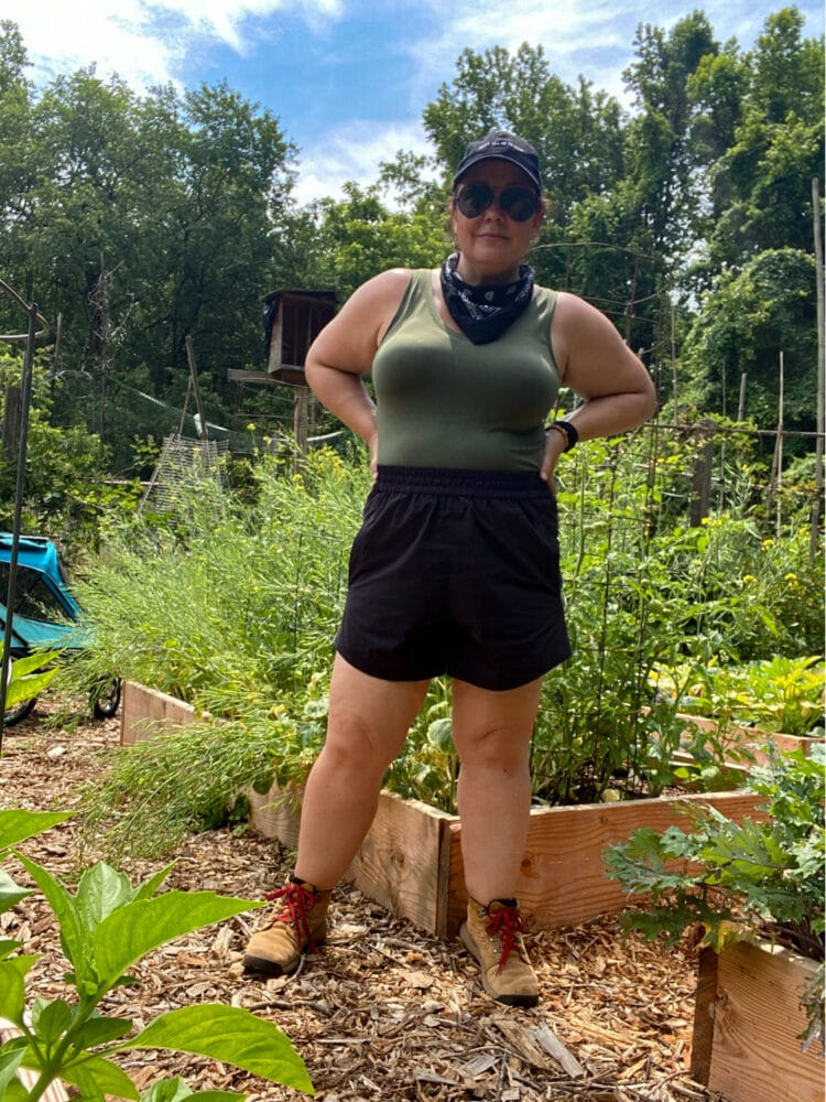 Wearing the Universal Standard Sunny shorts in black in my garden. They are styled with a navy v-neck tank, black bandana and tan Danner hiking boots