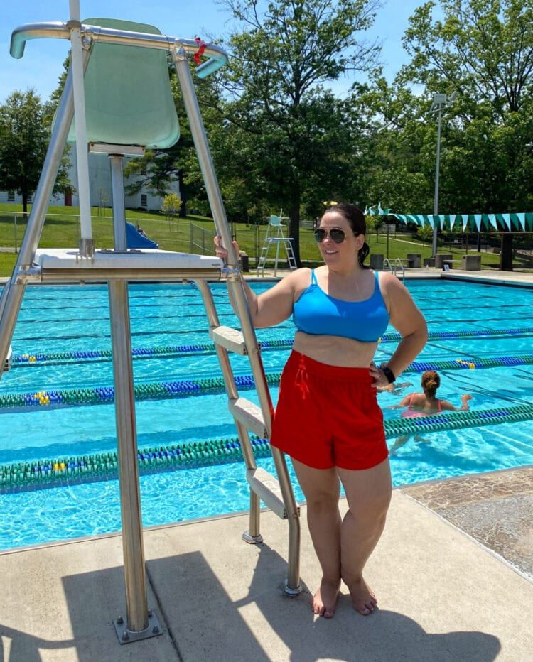 Alison in the Universal Standard Sunny Swim Shorts in red with a turquoise bikini top. She is standing in front of a public swimming pool wearing Ray-Ban aviators.