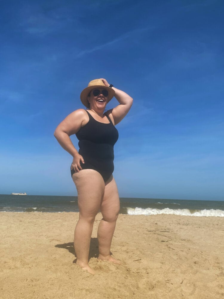 Alison in the Lands' End Tugless Tank swimsuit in black. She is standing on the beach with her hand on her head laughing to the camera.